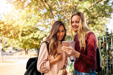 Female students using cellphone on road