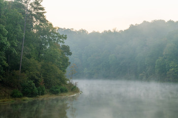 Fog rises from the calm morning water of a small reservoir near Oxford, Alabama, USA