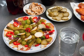 Party platter with piece of cheese, grape, cucumber and ham, water and vine on table.