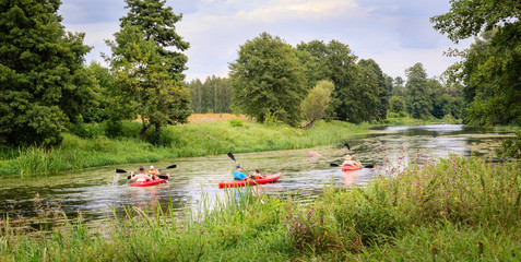 Kayaking on a river among forest and meadows