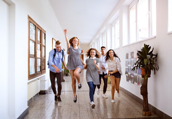Teenage students in high school hall jumping high.