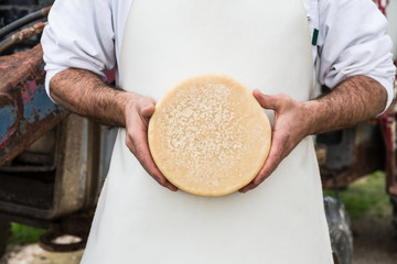 Man holding traditional cheese
