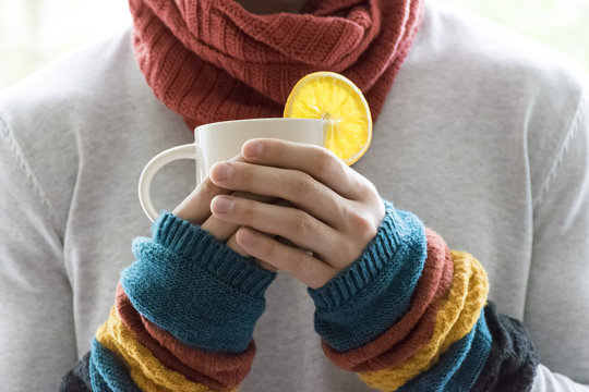 A young man holding a Cup of tea and lemon. Cold, cold, disease.