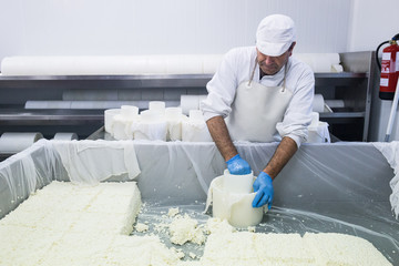 Man in uniform producing cheese of fresh raw materials in workshop of cheese factory.