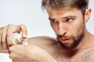 man squeezes cosmetic cream on hand