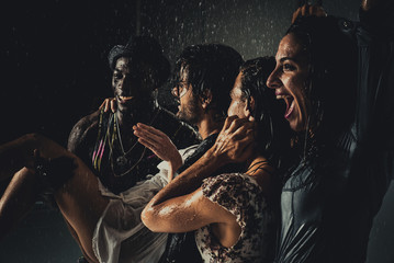 Group of friends dancing in the rain