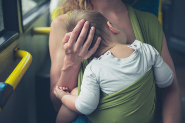 Mother breastfeeding baby on the bus