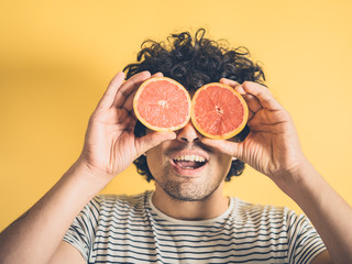 Silly young man using grapefruit as binoculars