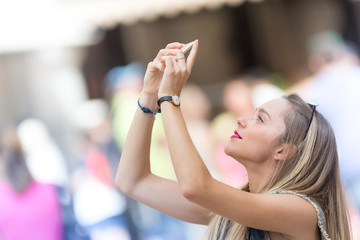 Pretty blonde teenager taking a photo with her mobile phone