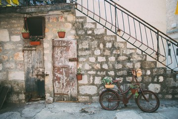Side of building and stairs made from old bricks and wooden doors decorated with plants hanging, old painted vintage bike, concept provence design, lifestyle, rustic