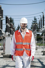 Portrait of engineer against electricity substation