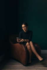Woman sitting in armchair, looking at smartphone