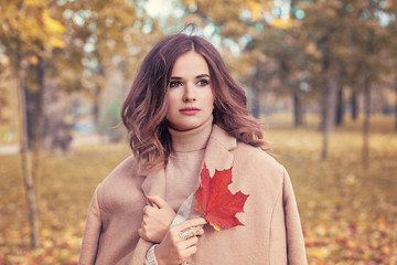 Perfect Woman with Yellow Autumn Leaf in hear Hand Outdoors. Beautiful Fashion Model wearin Coat in Autumn Park