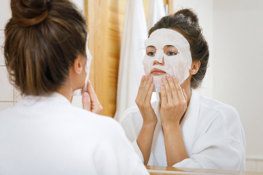 Woman is applying sheet mask on her face