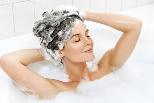 Woman is washing her hair with shampoo