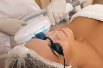 Beautiful woman in beauty salon during photo rejuvenation procedure