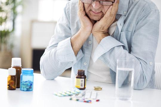 Old man looking at pills desperately