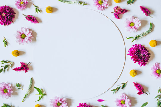 A bright creative pattern of fresh flowers and leaves with copy space. Natural background. Frame of flowers. Flat lay.