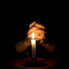 Hands and candle. Prayer, mercy, faith concept.