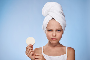 girl in towel holding a sponge for removing makeup on blue background, portrait