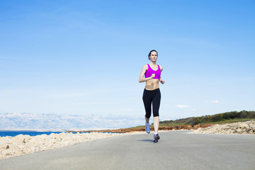 Young woman running on waterfront path