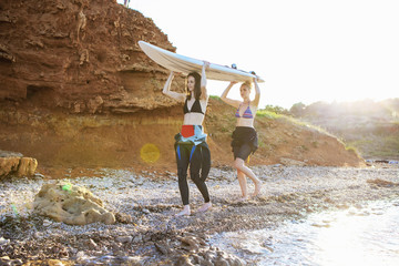 Female surfers carrying surfboard