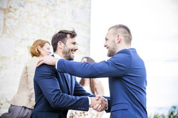 Bridegroom shaking hands with friend
