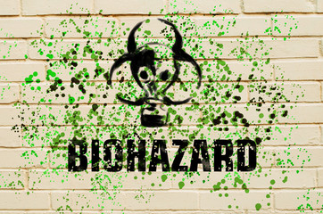 Biohazard sign in the form of a gas mask on the wall with green spatter
