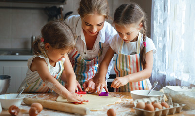 Happy family mother and children twins   bake kneading dough in kitchen.