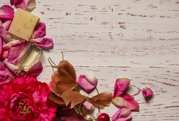 Wooden background framed with petals and pink accessories