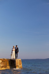 Bride and groom standing on pier against blue sky