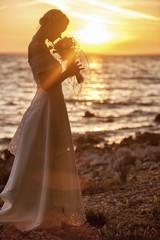Bride smelling bouquet against sunset
