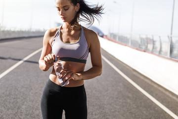 Front view of a fitness model taking a break, opening water bottle