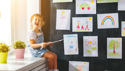 child girl hanging her drawings on wall
