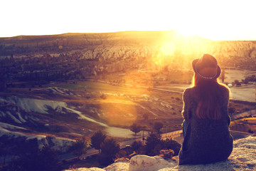 A tourist girl in a hat sits on a mountain and looks at the sunrise.