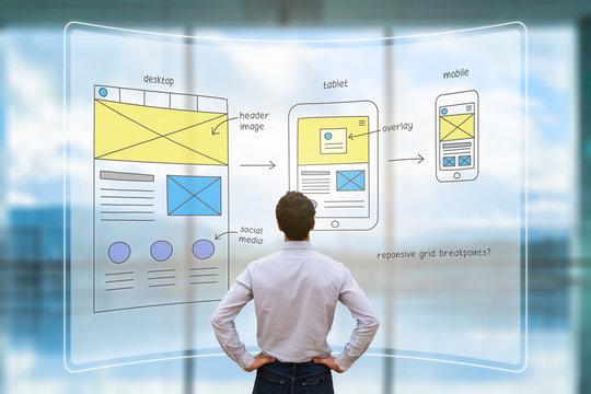 Website front end designer reviewing wireframe layout mockup, AR screen