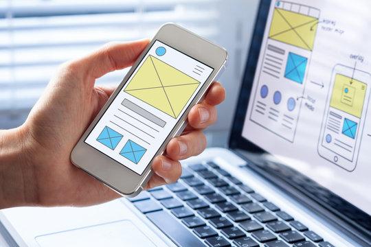 Mobile responsive website development, wireframe design preview on smartphone screen