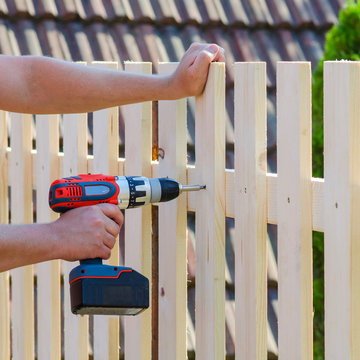 Man hands building wooden fence with a drill and screw. DIY concept. Close up of his hand and tool.