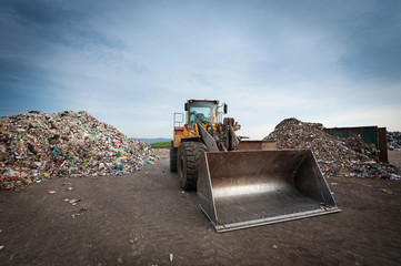 Bulldozer in front of pile of waste at city landfill.