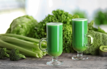Glasses of green healthy juice with vegetables on wooden table