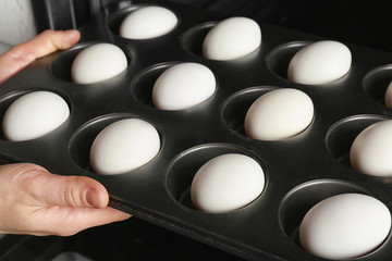 Woman putting muffin tin with eggs into oven