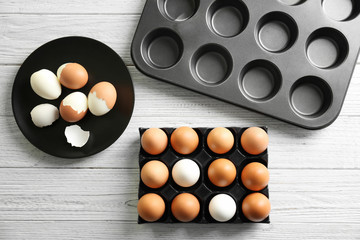 Holder and plate with hard boiled eggs on wooden table