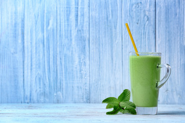 Glass of green healthy juice with mint on wooden table