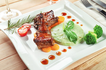 Plate with delicious ribs and mushy peas on table