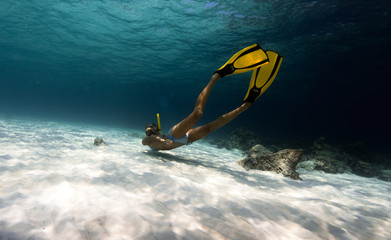 Woman freediver explores tropical underwater world, glides over sandy bottom among the rocks