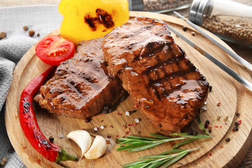 Wall Mural - Tasty grilled steaks on wooden board