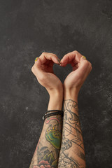 Female hands with tattoos in shape of heart