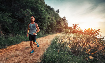 Athletic man runs on a rural tropical road during sunset Wall mural