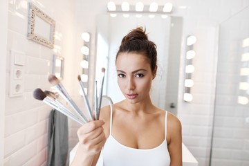 Young woman holding makeup brushes