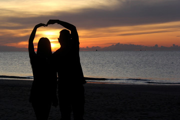 silhouette of romantic honeymoon couple on the beach